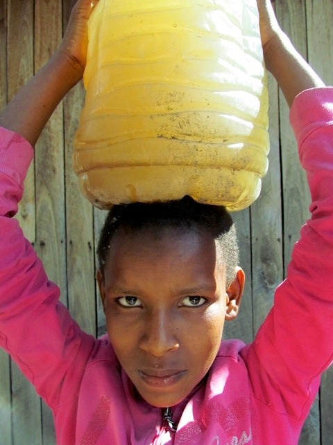 """Prior to the donation of 10,000 liter rainwater storage tank, students like Naini Rarin (pictured above) had to walk great distances to collect bacteria filled river water for drinking"""