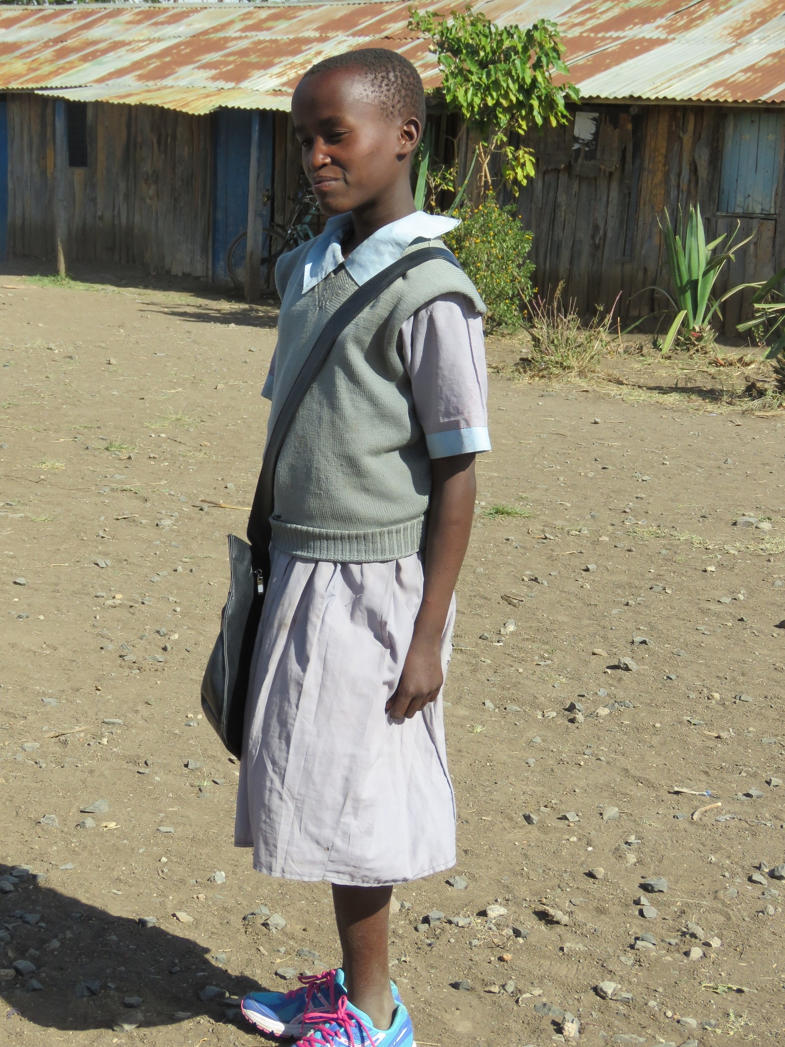 Standing outside of Matanya Primary School, Nancy is overjoyed with the gift of shoes and a book bag.