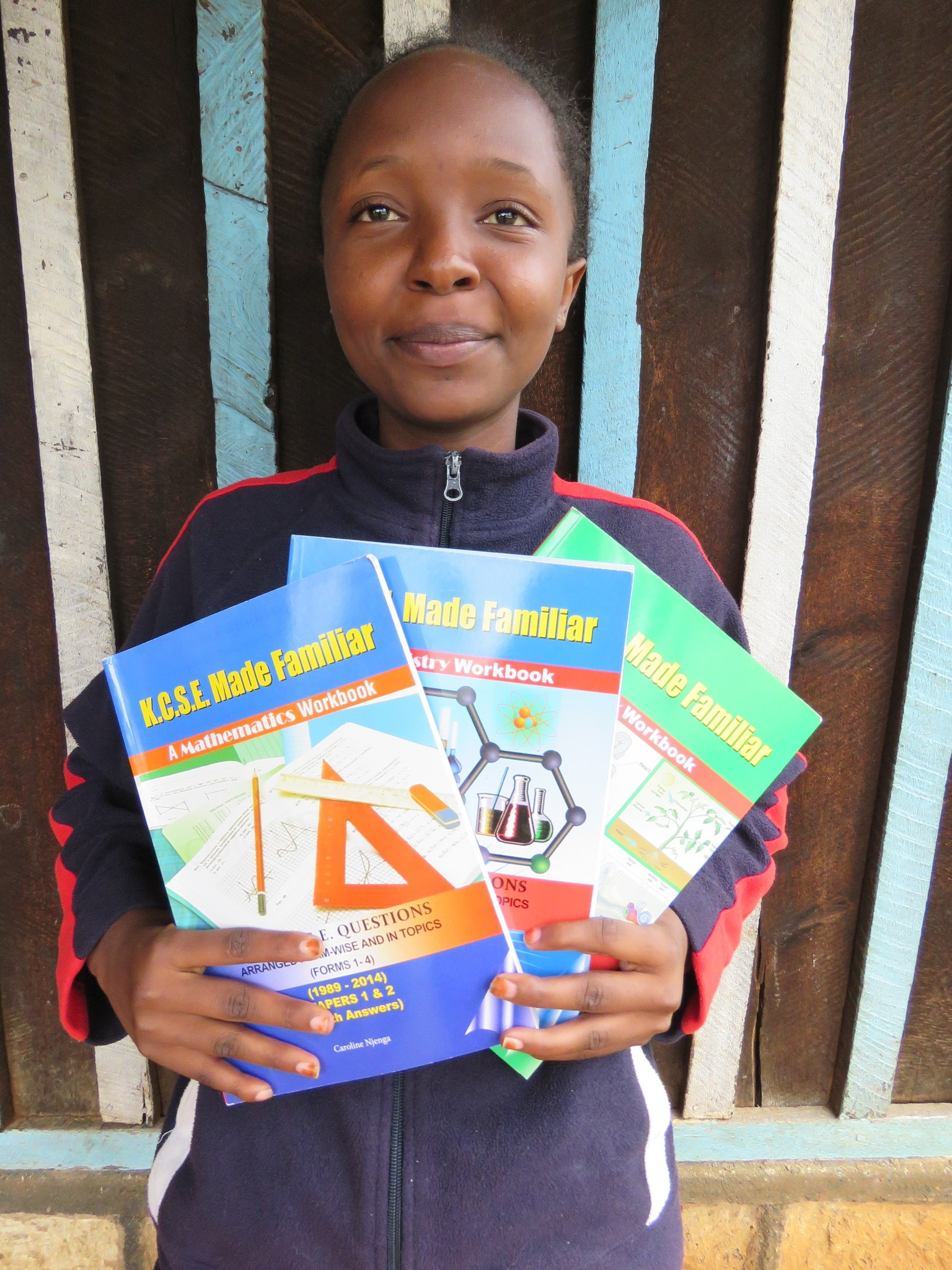 In addition to her sponsor gifts, Linet receives 3 revision books she requested to aid her in her studies.