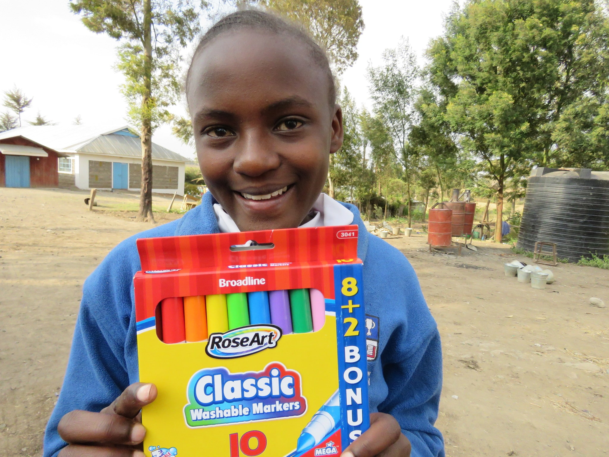 Rose Muthoni receives stationary, notebooks and markers from her sponsors during the 2015 mission.