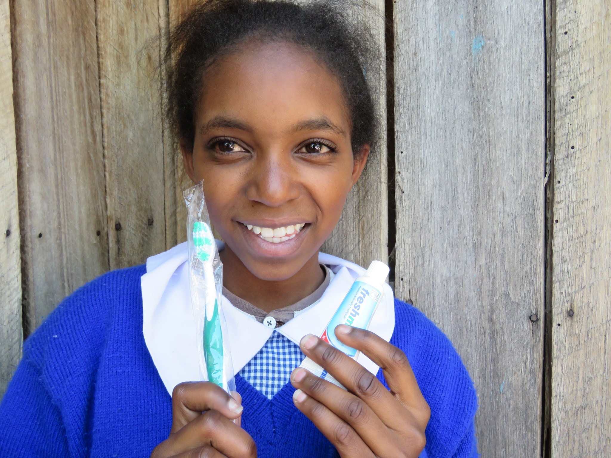 Moreen holding toothbrush and toothpaste, some of the many items donated to her for school.