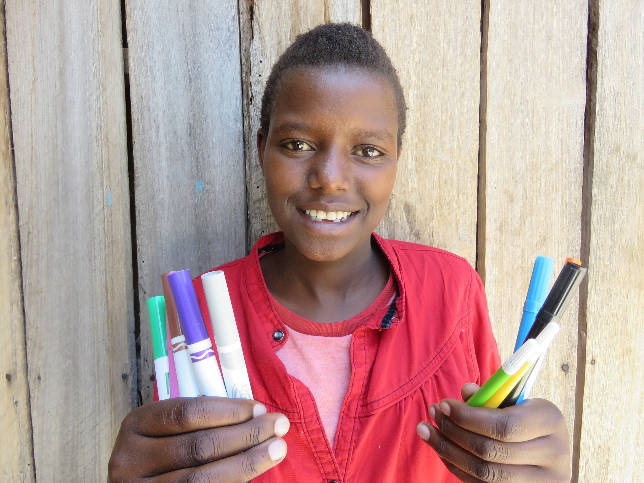 Taiyana holding a new set of markers for school.