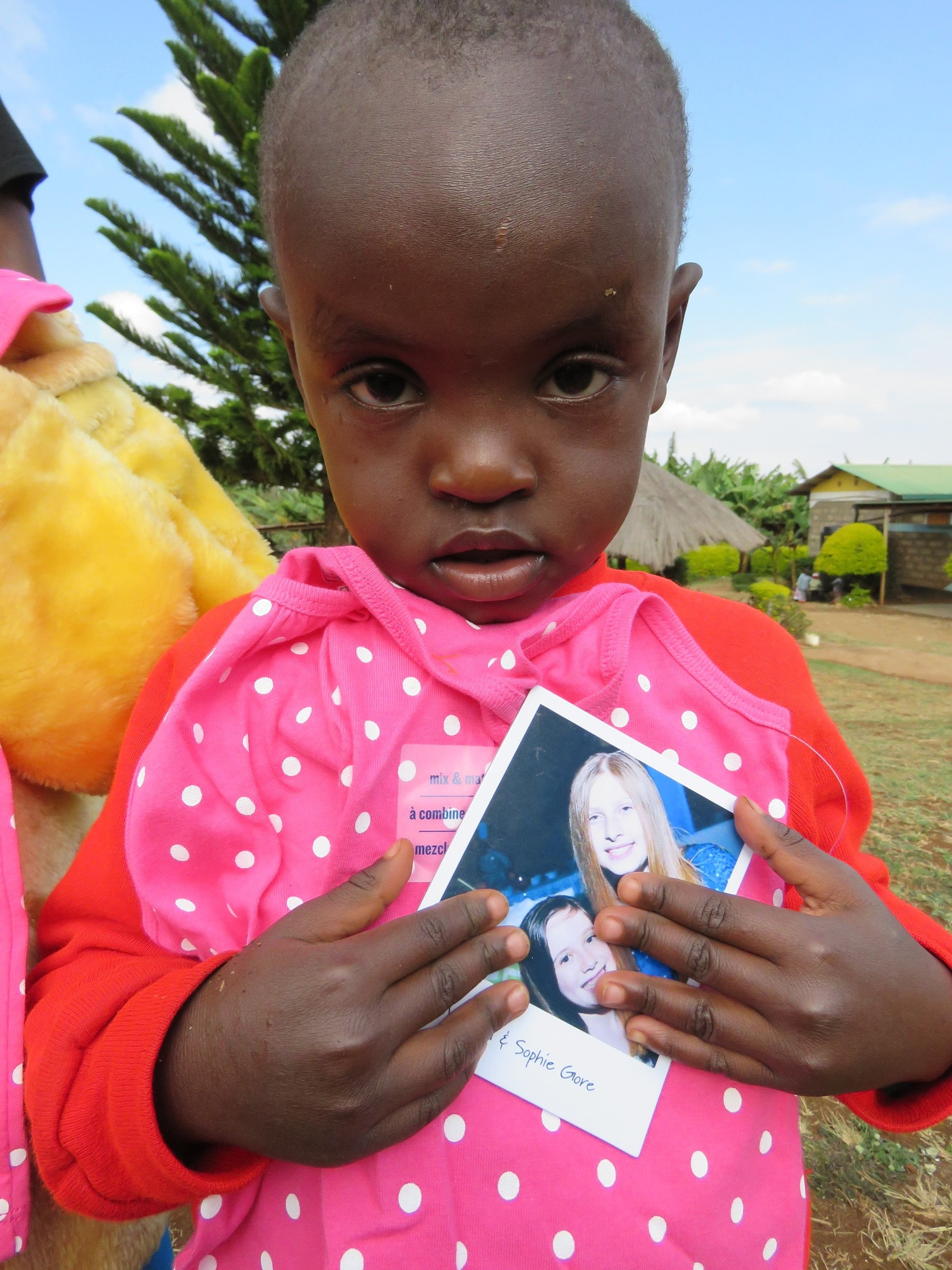 This little orphaned girl is holding our picture - and behind that is a pair of pajamas we donated for her to wear.