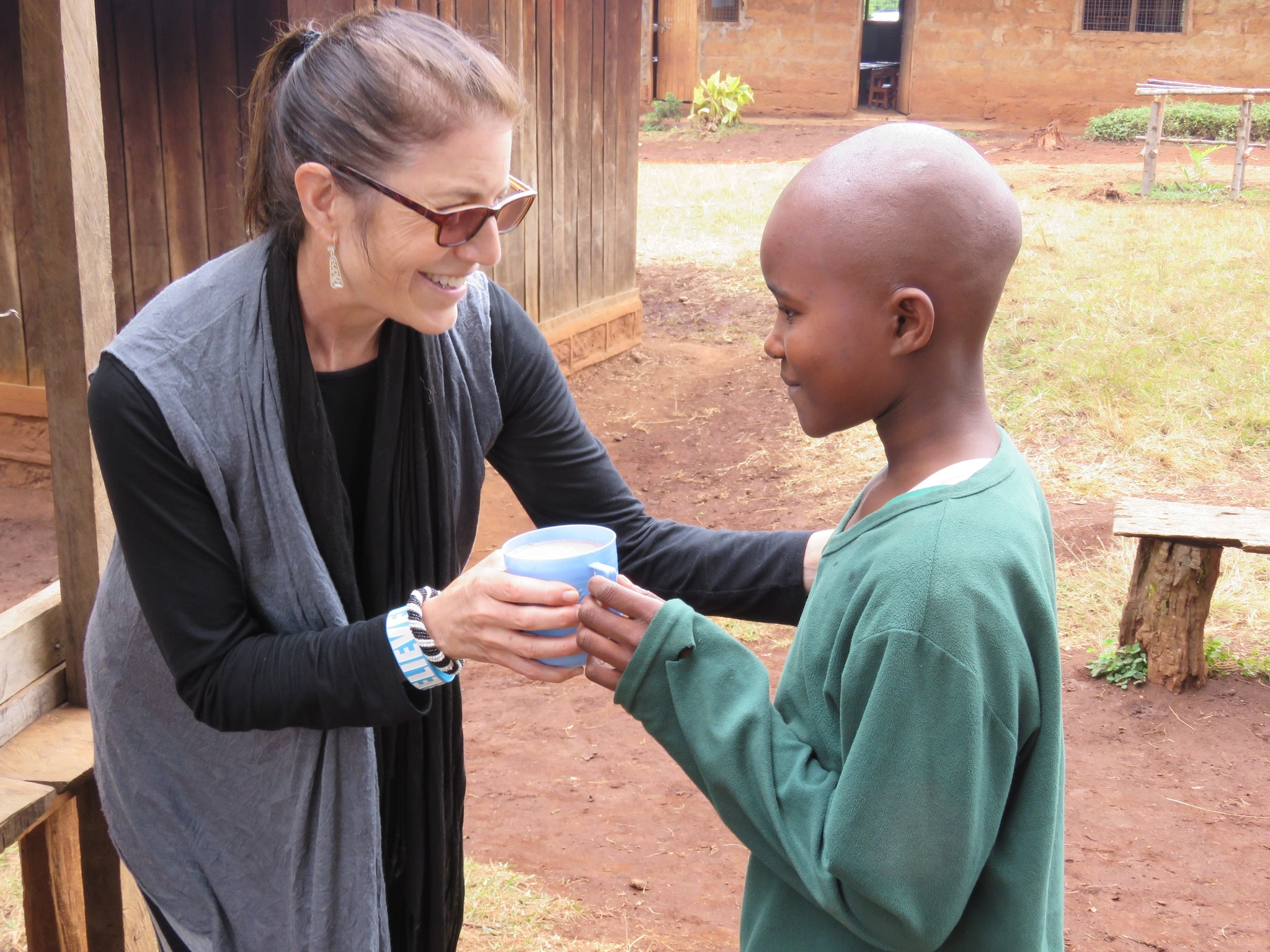 Matanya's Hope founder Michelle Stark serves a child from Kagaani Primary school with porridge.  For many of these students, this porridge is the only meal they will receive in a day.