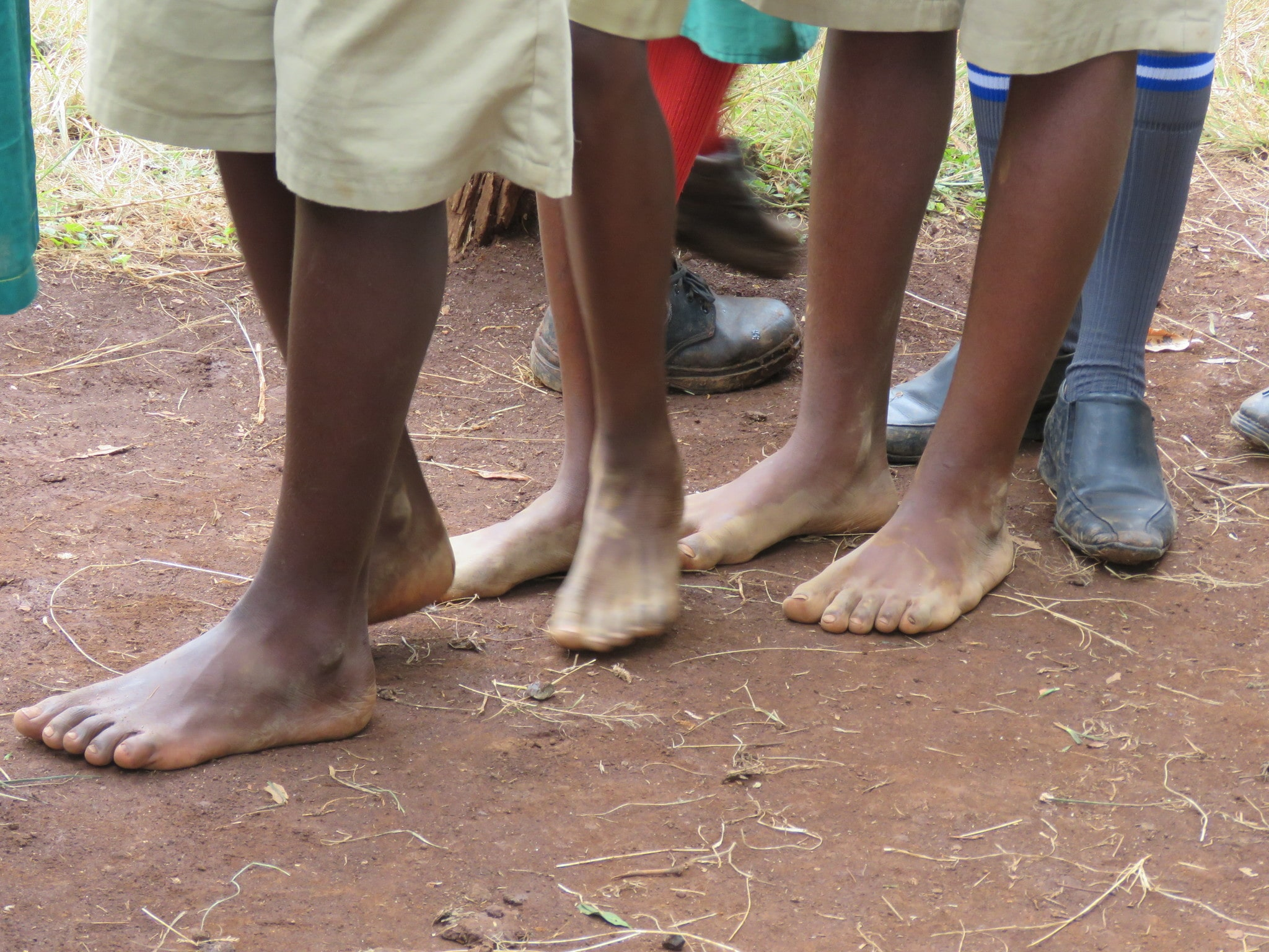 Children wait in line for distribution of porridge, school supplies and shoes.