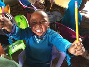 Little boy in nursery school (baby class) receives school supplies.  He is as happy as the sun is hot!