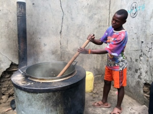 Young boy at Jamii children's center (orphanage) cooks beans and maize.  Well wishers make the food possible.