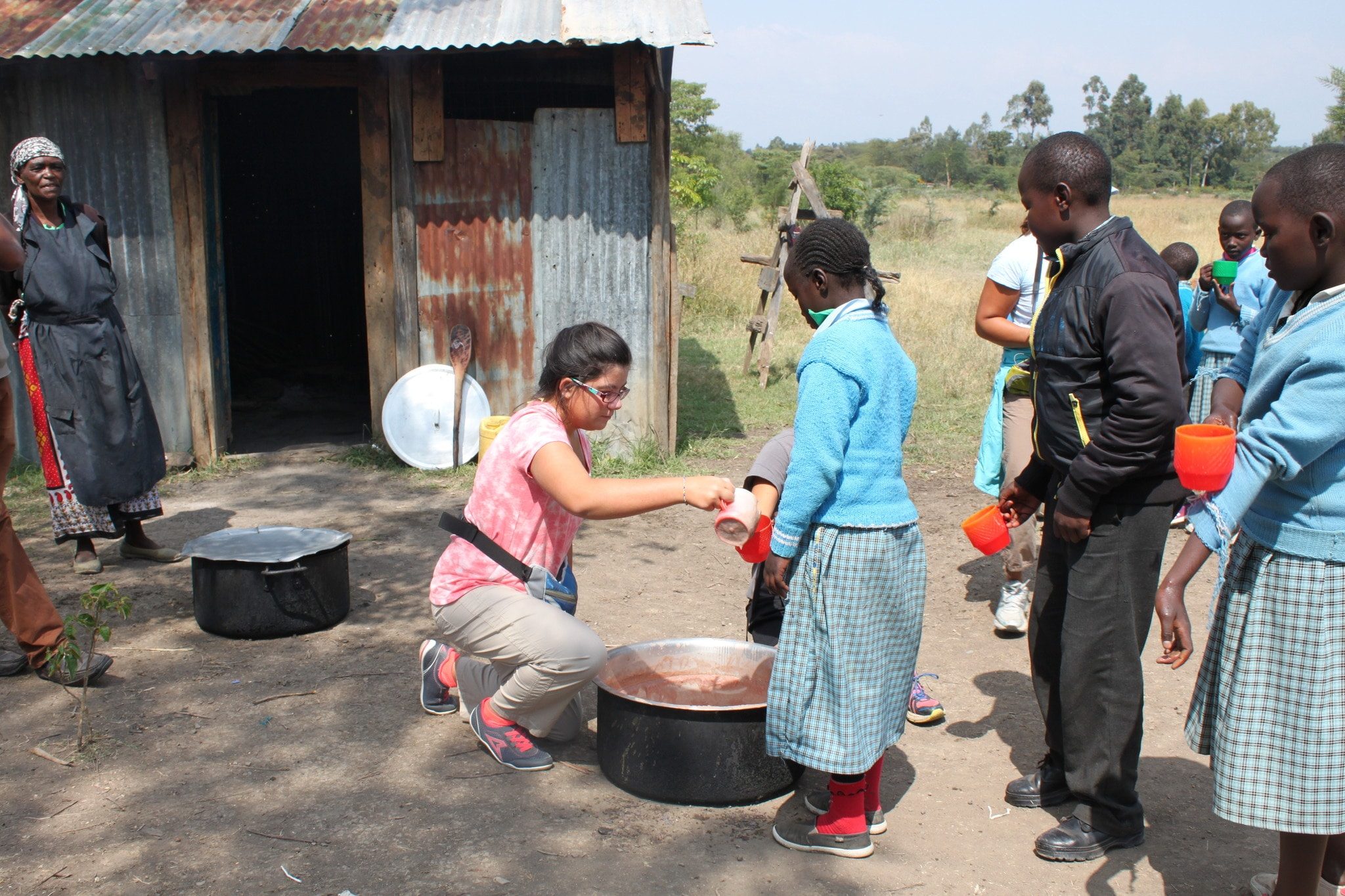 Mission  participants embrace the opportunity to serve porridge to the children.