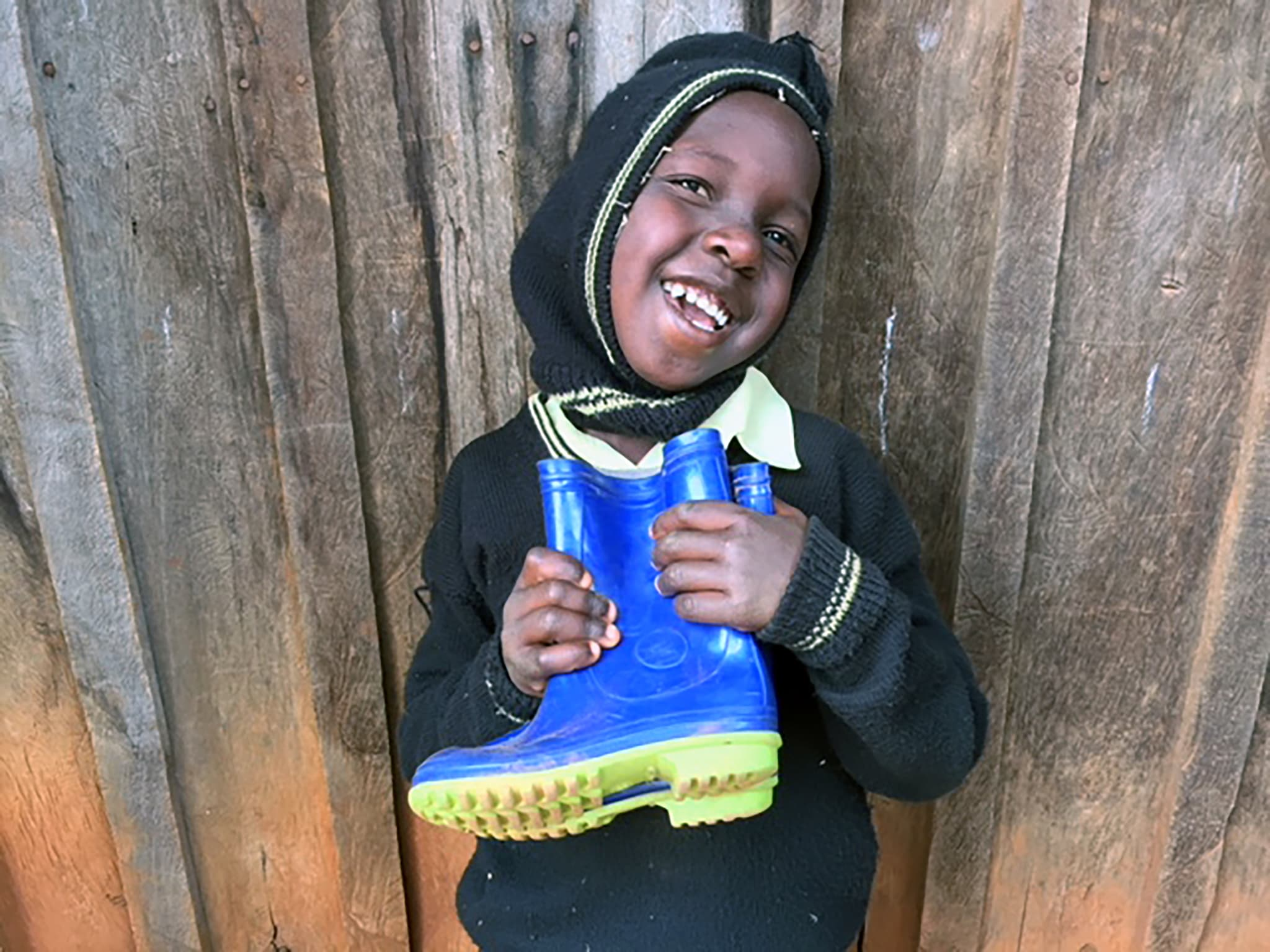 A boy receiving clothing and boots at Kagaani Primary School.