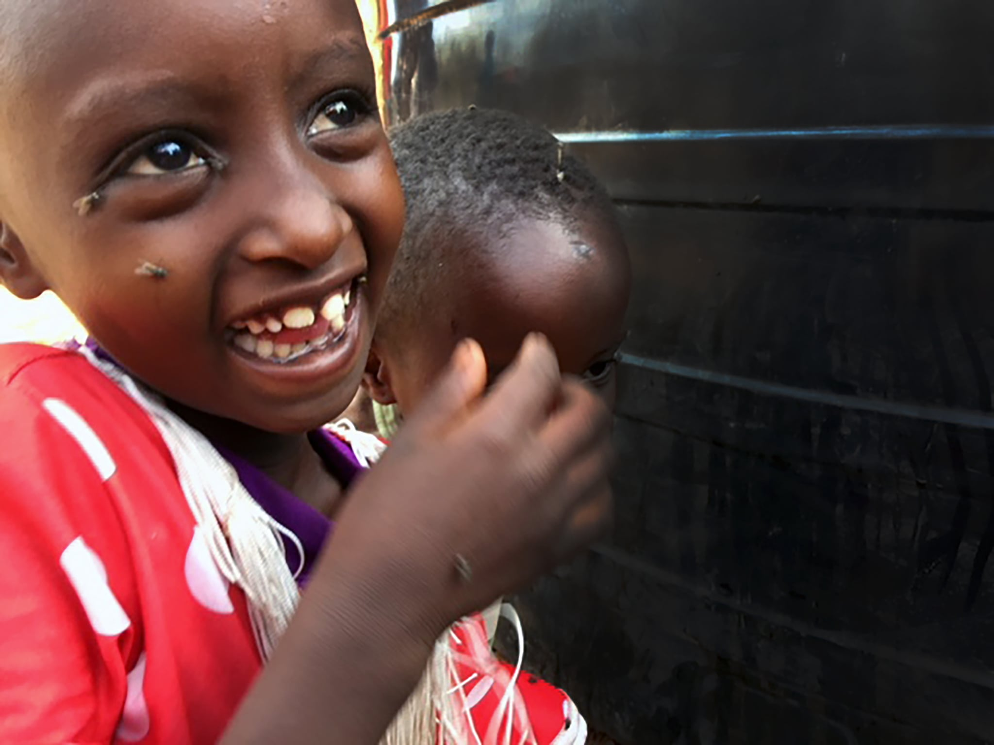 This little girl is so excited as their newly donated tank is being filled with safe water.