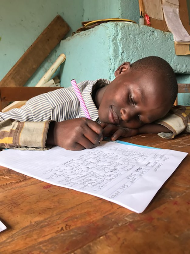 This is John.  Just a few months ago, he was sleeping cold and hungry, on a dirt floor.  He was frequently subjected to homelessness; his mother could not afford $3 rent.  Today, he finds joy in writing to his sponsor and in attending school.