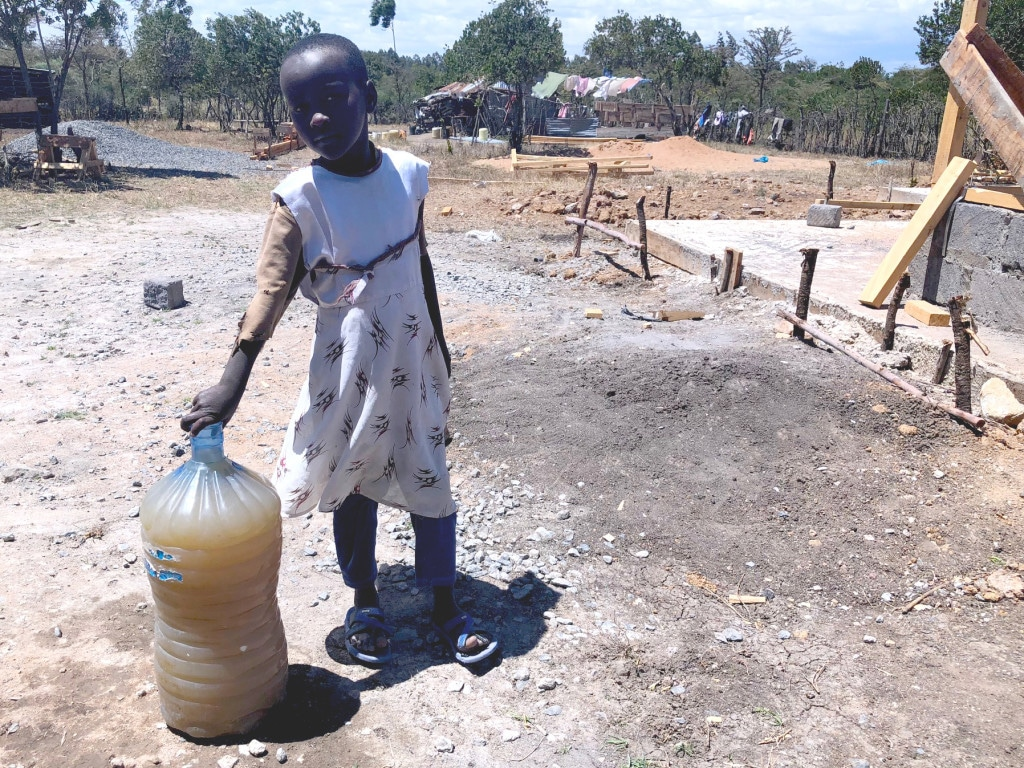 Young Sabina stands by a bottle of water her family recently collected from a nearby river.  Her family will drink, bath  with and cook with this water.