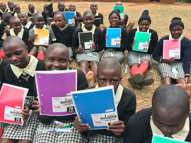 School children are given notebooks and pens, something Alan and Erick want so desperately.