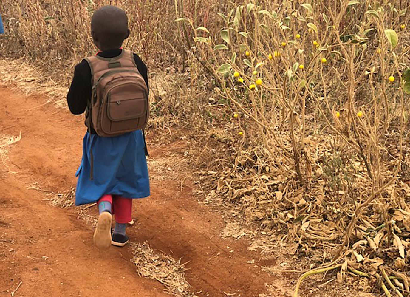 Child walking home from school in rural Kenya